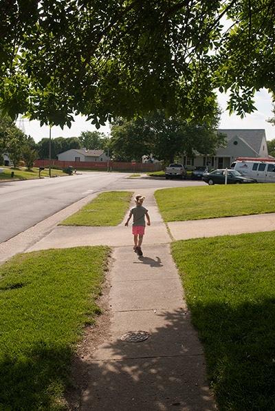My daughter running away down the sidewalk